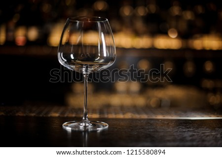 Elegant and empty burgonya glass on the bar counter in the background of bar lights #1215580894
