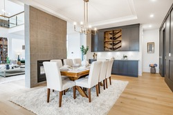 Elegant and large staged dining room with dark cabinets and walls.