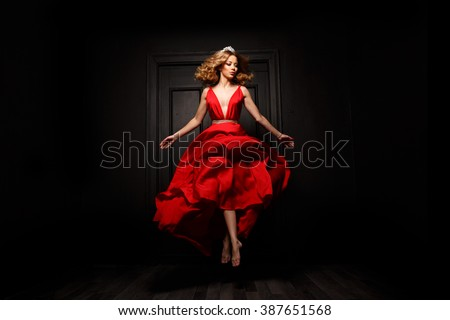 Elegant and passionate woman with tiara on her head in the red evening fluttering dress is capture in move, hovering above the ground, the wooden door is on the background