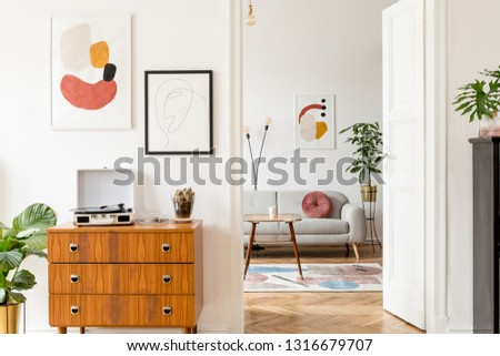 Elegant and retro decor of living room with design commode, coffee table vinyl recorder, cacti and mock up posters frames on the white walls. Cozy room with brown wooden parquet and plants.