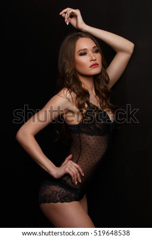 Elegant and seductive woman with wavy hair, slim beautiful figure and glowing smooth skin is posing in the black translucent lace lingerie in the studio near the wall, dark background, backlight #519648538
