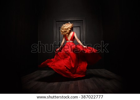 Elegant and sexy woman in the red evening fluttering dress is capture in move, running away from the ceremony (the  ball), the wooden door is on the background