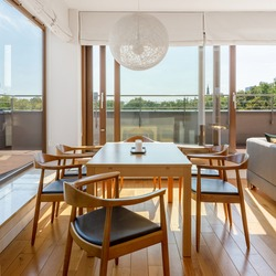 Elegant and simple wooden dining table and six chairs and window wall