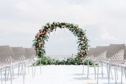 Elegant and stylish decor wedding ceremony on the sea. The round wedding arch is decorated with a variety of fresh flowers and greens.