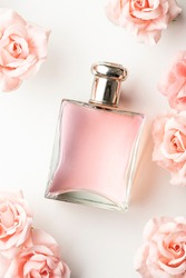 ELEGANT AND STYLISH FLORAL ARRANGEMENT WITH PINK ROSES AND FRAGRANCE BOTTLE ON WHITE BACKGROUND. ADVERTISING CONCEPT FOR WOMEN'S PERFUMES. TOP VIEW.
