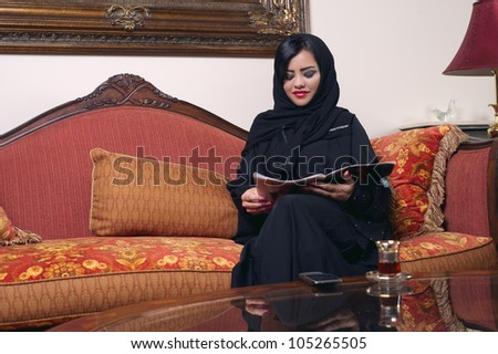 elegant arabian lady with hijab relaxing in salon reading magazine