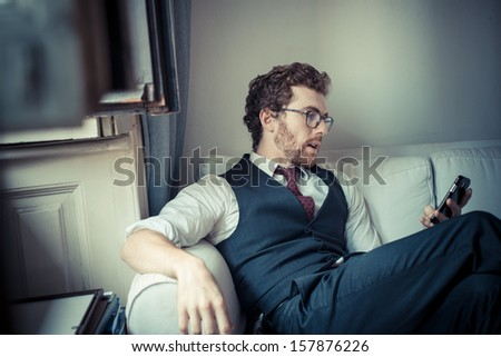 elegant attractive fashion hipster man on the phone at home