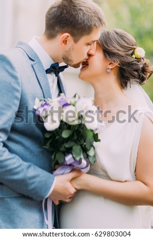Elegant attractive newlywed couple kissing outdoors in the park with rose bouquet between them #629803004