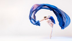 Elegant ballerina in pointes dances with a developing blue cloth on a white background