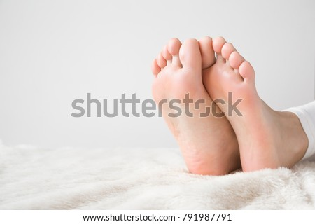 Elegant bare feet. Beautiful groomed woman's feet on the fluffy blanket. Cares about clean and soft legs skin. Lying and enjoying rest. #791987791