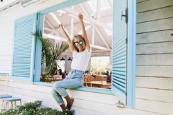 Elegant barefooted girl sitting on window sill and waving hands. Photo of pleased blonde woman in jeans and white t-shirt expressing energy in sunny day.