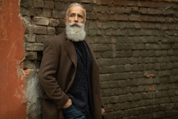 Elegant bearded man. Closeup side view of one handsome senior man with grey hair and long lush beard in coat standing outdoor on stone wall.