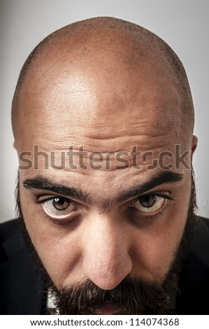 elegant bearded man showing his baldness on white background
