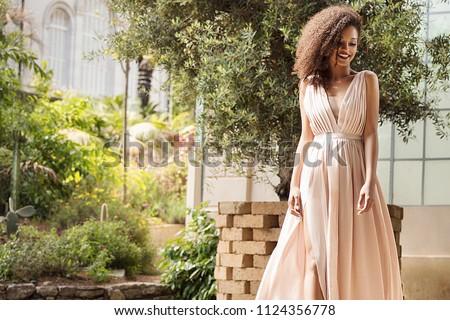 Elegant beautiful african american woman posing in maxi dress outdoor.