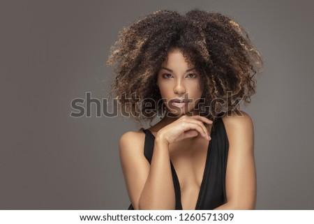 Elegant beautiful african american woman posing in sexy black dress. Studio shot.