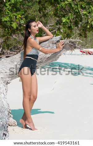 Elegant Beautiful Asian Thai Woman Girl with perfect body Fashion Swim Suit at sand Ocean Beach, old age Timber tree and Kayak Canoe #419543161