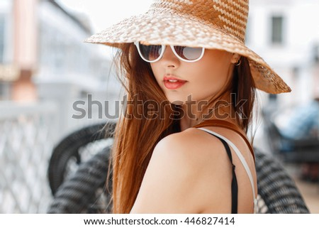 Elegant beautiful woman in stylish vintage straw hat and white sunglasses resting on a sunny day. #446827414