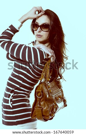 Elegant beautiful woman with fanning hairs and sunglasses-light blue background