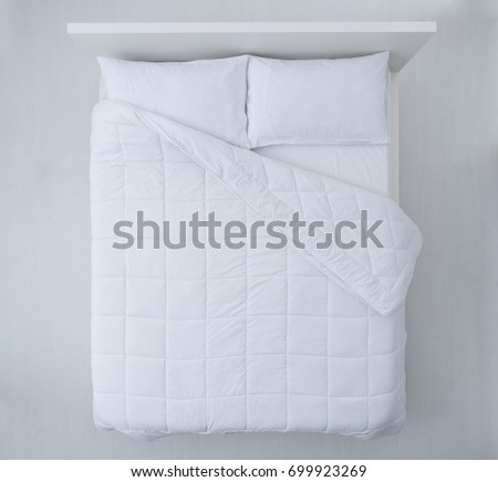 Elegant bed with soft white duvet, bedding and pillows, top view