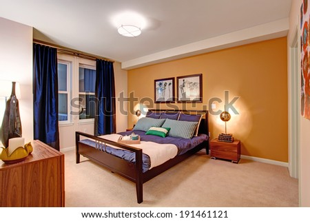 Elegant bedroom with black wooden bed covered in purple bedding