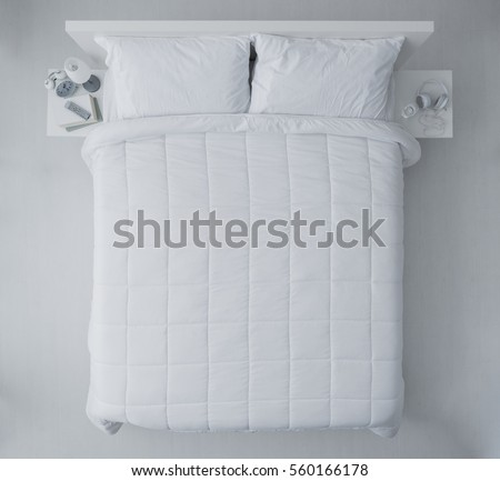Elegant bedroom with white duvet and sheets, top view