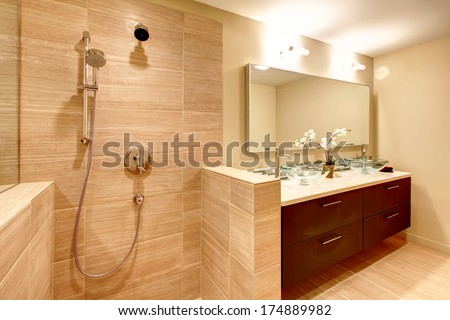 Elegant beige bathroom with shower. Glass vessel sinks  perfectly match with white flowers, brown wood cabinets and mirror
