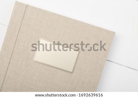Elegant beige book with linen cover and metal nameplate. Wedding photobook. Wedding photo album Сток-фото ©