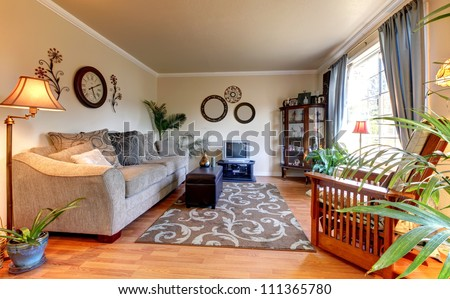 Elegant beige living room with blue and old  mall TV and hardwood floor.