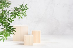 Elegant beige wooden cube podiums with green lush foliage in sunlight on white board and grey marble wall for product display. Simple modern summer design.