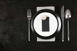 Elegant black and white table setting: plates, gray polka dot napkin, blank label with rose and silverware. Top view point.