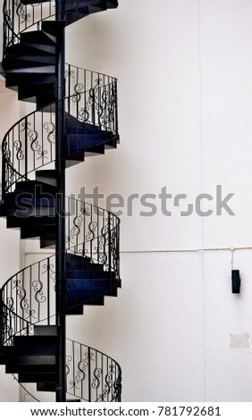 Elegant black metal spiral staircase on the side of a town house in historic Geylang, Singapore  #781792681