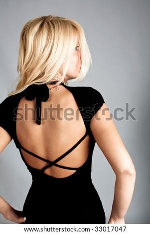 elegant blond woman in black dress, back view, studio shot