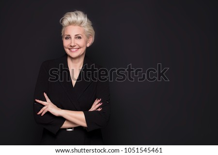 Elegant blonde beautiful middle aged lady posing,smiling to the camera. Attractive businesswoman.