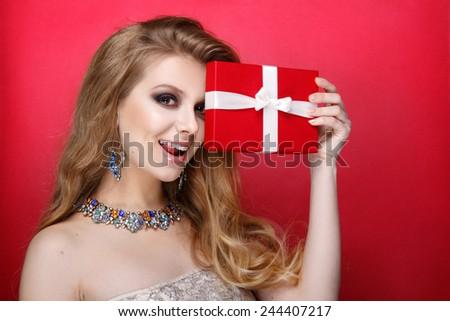 Elegant blonde woman holding small gift box with ribbon. Studio portrait over red background. Happy birthday. Valentines Day. Joyful