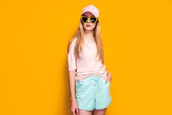 Elegant blonde woman wearing fashion cap, sunglasses enjoying sun on yellow summer background