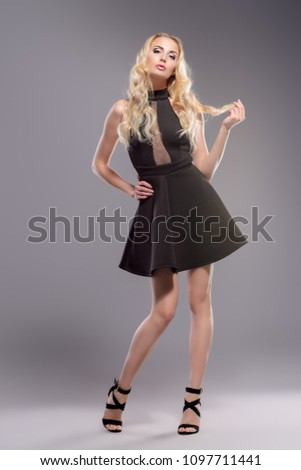 Elegant blonde young woman wearing black dress. Beauty, fashion concept. Full length portrait. Studio shot. #1097711441