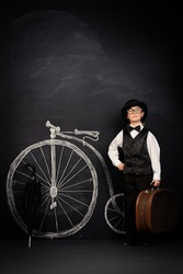 Elegant boy in a suit, bowler hat and glasses stands by a painted retro bicycle. Old Europe style, England. Little gentleman. Kid's fashion.