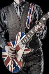 elegant brit pop guitarist playing a british flag guitar