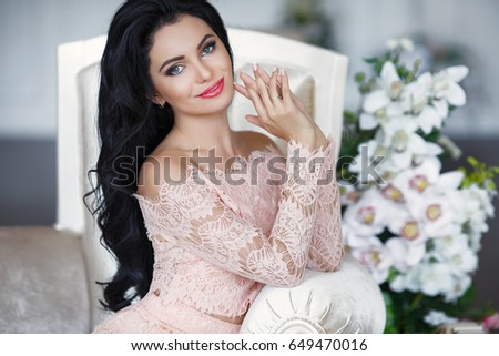 Elegant brunette woman in beige lace dress posing on sofa. Beautiful fashion model with long dark hair wear stylish dress smiling at camera in interior.