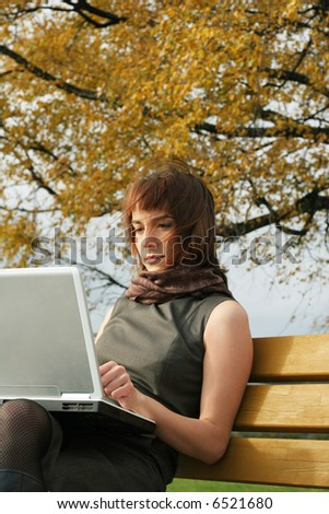 Elegant brunette woman sitting with laptop on the bench in the autumn park - stock photo