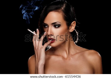 Elegant brunette woman smoking a cigarette on black background