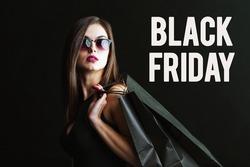 Elegant brunette woman wears sunglasses and black dress holding black shopping bags, black friday concept