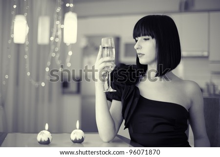 elegant brunette woman with glass of drink sitting at the table, celebrating