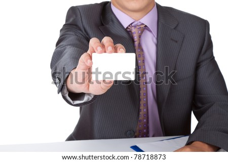 Elegant Business man dressed in suit, shirt and tie, handing a blank business card, isolated over white background. Sitting at the office desk. Meeting concept
