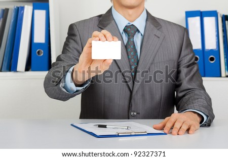 Elegant Business man handing a blank business card, dressed in suit, shirt and tie, Sitting at the office desk. Meeting concept