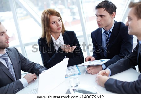 Elegant business partners listening to colleague at meeting - Shutterstock ID 140079619