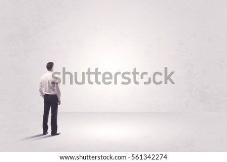 Elegant business person standing with his back looking at big empty white space concept #561342274