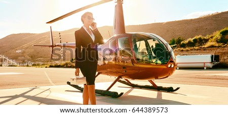 Elegant business woman talking by phone near the helicopter. Business, success and luxury concept