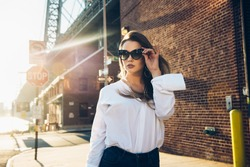 Elegant business woman wearing sunglasses and white t-shirt at hot summer day in the city