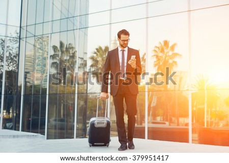 Elegant businessman checking e-mail on mobile phone while walking with suitcase outside airport, experienced male employer using cell telephone while waiting for taxi car outdoors before work travel